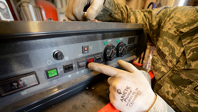 An Airman turns off a boiler to a dormatory